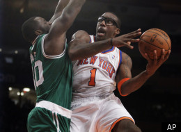 New York Knicks power forward Amare Stoudemire (1) tries to shoot around Boston Celtics power forward Brandon Bass, left, in the first half of their NBA basketball game at Madison Square Garden in New York, Sunday, Dec. 25, 2011. (AP Photo/Kathy Willens)