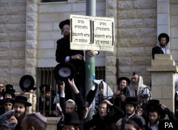 Ultra-Orthodox Jewish men gather around a sign that reads in Hebrew: