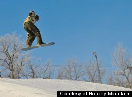 A snowboarder catches some air on the slopes of Holiday Mountain.