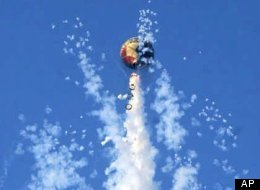 Fireworks hanging from an unmanned paper balloon explode over Rio de Janeiro, Brazil.