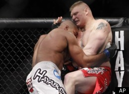 Brock Lesnar is pushed into the octagon by Alistair Overeem of the Netherlands during their UFC heavyweight mixed martial arts match Friday, Dec. 30, 2011 at The MGM Grand Garden Arena in Las Vegas. Overeem won TKO when the fight was stopped by the referee. (AP Photo/Eric Jamison)