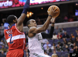 Boston Celtics guard Rajon Rondo, right, goes to the basket against Washington Wizards guard John Wall (2) during the first half of an NBA basketball game, Sunday, Jan. 1, 2012, in Washington. The Celtics won 94-86. (AP Photo/Nick Wass)