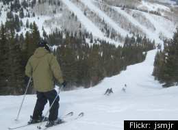 A skier helps a snowboarder find his balance at Park City Mountain.
