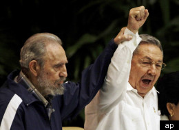 Fidel Castro, left, raises his brother's hand, Cuba's President Raul Castro, center, as they sing the anthem of international socialism during the 6th Communist Party Congress in Havana, Cuba, Tuesday April 19, 2011. Raul Castro was named first secretary of Cuba's Communist Party on Tuesday, with his brother Fidel not included in the leadership for the first time since the party's creation 46 years ago. (AP Photo/Javier Galeano)