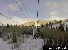 Snowboarders ride the lift up the mountain Canyons Resort.