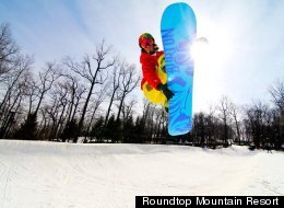 A snowboarder makes a jump at Roundtop Mountain Resort in Pennsylvania.