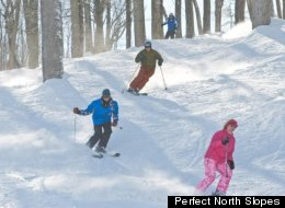 Skiers make their way through the trees at Perfect North Slopes.