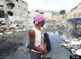 A Haitian woman waiting for a taxi in Port-au-Prince looks at earthquake damage on January 9, 2012.