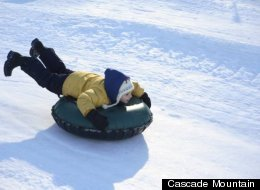 A boy speeds down one of the lanes, headfirst, at Cascade Mountain's Snow Tube Park.