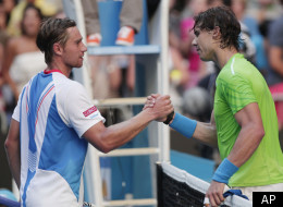 Spain's Rafael Nadal shakes hands with Alex Kuznetsov, left, of the US following their first round match at the Australian Open tennis championship, in Melbourne, Australia, Monday, Jan. 16, 2012. (AP Photo/Rick Rycroft)