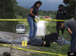 In this Wednesday Oct. 5, 2011 photo, the bodies of three people, who police allege are gang members who were killed by unidentified assailants, are inspected by a forensic team in the village of Los Hornos, Honduras, 20 kilometers (13 miles) south of Tegucigalpa. Honduras has become a main transit route for South American cocaine, a trend that has helped drive the country's homicide rate to the highest level in the world and left many villages dependent on the cocaine trade. (AP Photo/Fernando