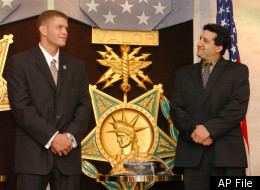 Eric M. Jones, left, and Steve DeChiaro stand in front of the Medal of Valor during an awards ceremony at the Pentagon in Washington Monday, July 15, 2002. Both men were honored for their efforts after the Sept. 11 terrorist attack. The Medal of Valor, the highest award given to civilians by the Department of Defense, recognizes acts of heroism in the face of danger. (AP Photo/Evan Vucci)