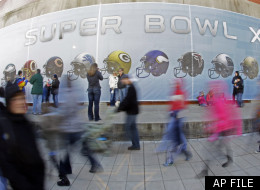Fans walk by a wall decorated with football helmets as others stop to take pictures at the Super Bowl Village on Saturday, Jan. 28, 2012, in Indianapolis. Super Bowl Village includes activities, attractions and music in conjunction with Super Bowl XLVI, which will feature the New England Patriots facing the New York Giants on Feb. 5. (AP Photo/Mark Humphrey)