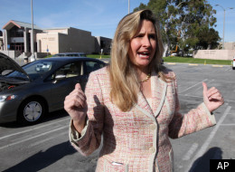 Heather Peters, who says her 2006 Honda Civic Hybrid, rear, never achieved the 50 mpg Honda claimed in its advertising, talks with reporters outside small claims court in Torrrance, Calif., Tuesday, Jan. 3, 2012. Peters has opted out of a class action settlement agreed to by Honda because it does not provide enough remuneration. (AP Photo/Reed Saxon)