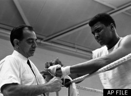 World Heavyweight Boxing champion Cassius Clay, Muhammad Ali, looks on impassively as his hands are taped by trainer Angelo Dundee before sparring with Jimmy Ellis, unseen, during a training session at the Territorial Army Centre in White City, London, on May 10, 1966. This was Clay's first training session since his arrival in England for the defence of his World Heavyweight title against Britain's Henry Cooper, unseen. (AP Photo/Kemp)