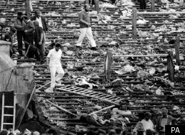 Shocked spectators walk through the personal belongings of victims littering the stands, after the disaster at Heysel Stadium in Brussels