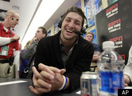 Denver Broncos quarterback Tim Tebow, left, laughs during an interview on radio row at the Super Bowl XLVI media center Thursday, Feb. 2, 2012, in Indianapolis. The New England Patriots will face the New York Giants in Super Bowl XLVI Feb. 5. (AP Photo/David J. Phillip)