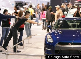 An onlooker is restrained from a Nissan display at the 2011 Chicago Auto Show.
