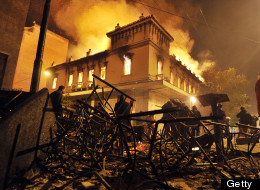 A fire engulfs a store during clashes between protesters and riot police near the Greek parliament in Athens on February 12, 2012. (Photo credit should read LOUISA GOULIAMAKI/AFP/Getty Images)