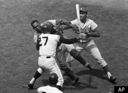 San Francisco Giants pitcher Juan Marichal (27) swings a bat at Los Angeles Dodgers catcher John Roseboro in the third inning at Candlestick Park in San Francisco, Calif., on Aug. 22, 1965 when Marichal apparently felt Roseboro had thrown too close to his head. Los Angeles pitcher Sandy Koufax, rear, tries to break up the fight. Marichal was ejected and Roseboro was treated for facial cuts after the incident. (AP Photo/Robert H. Houston)