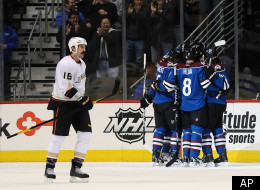 Anaheim Ducks right wing George Parros, left, skates past the Colorado Avalanche as they celebrate a goal by left wing Cody McLeod in the first period of an NHL hockey game on Monday, Feb. 27, 2012, in Denver. (AP Photo/Chris Schneider)
