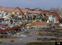 An employee of Henryville High School examines the remains of the building following severe storms