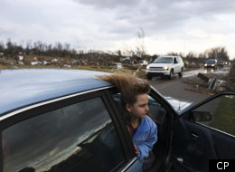Une jeune fille, cheveux dans le vent, observe l'ampleur des dégâts, dans la ville de New Pekin.  (AP Photo - Matt Stone)