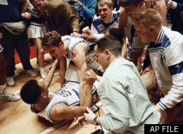 Duke's Christian Laettner, top, who scored the game-winning basket in overtime, celebrates with teammate Grant Hill on the floor of the Spectrum in Philadelphia Saturday, March 28, 1992, as teammates and fans crowd around. The defending national champions defeated the University of Kentucky 104-103 to advance to the final four. (AP Photo/Amy Sancetta)