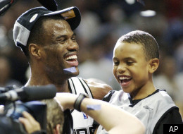 San Antonio Spurs' David Robinson holds his son Corey, 8, after the Spurs defeated the New Jersey Nets 88-77 to win the NBA Championship, Sunday, June 15, 2003.