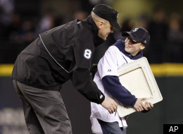 U.S. Army 1st Sgt. Steve Smerer surprises his son Kyle Smerer, 13, by dressing as an umpire and meeting the boy at second base during a base-stealing promotion between innings as the Seattle Mariners play the Oakland Athletics in a baseball game.