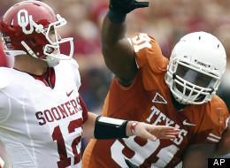 Oklahoma quarterback Landry Jones (12) passes under pressure from Texas defensive tackle Kheeston Randall (91) during the first half of an NCAA college football game at the Cotton Bowl in Dallas, Saturday, Oct. 8, 2011. (AP Photo/Mike Fuentes)