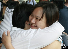 Chiranuch Premchaiporn, right, director of Thai newspaper website Prachatai, is greeted by an unidentified friend upon her arrival at the criminal court Monday, April 30, 2012, in Bangkok, Thailand. (AP Photo/Apichart Weerawong)
