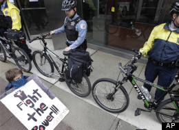 Chicago Police block the entrance to a Bank of America branch as about 50 Occupy Chicago activists gather outside, as part of a May Day demonstration, Tuesday, May 1, 2012, in Chicago. They accuse banks of profiting over the needs of ordinary people and decry Bank of America's federal bailout. (AP Photo/M. Spencer Green)