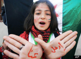 In this citizen journalism image provided by Edlib News Network (ENN), an anti-Syrian regime protester chants slogans against Syrian President Bashar Assad with Arabic on her hands that reads,
