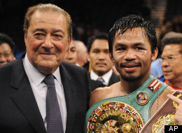 Manny Pacquiao, of the Philippines, center, holds his championship belt as he stands with promoter Bob Arum, left, and trainer Freddie Roach after winning his WBO welterweight boxing title fight against Miguel Cotto, Saturday, Nov. 14, 2009.