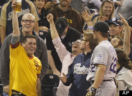 Colorado Rockies third baseman Jordan Pacheco, who lost a battle with a fan for a pop foul, looks at the fan holding up his beer where the ball ended up floating during the seventh inning of a baseball game Tuesday, May 8, 2012 in San Diego. (AP Photo/Lenny Ignelzi)