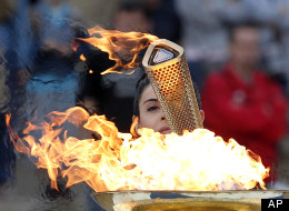 Actress Ino Menegaki, dressed as a high priestess, lights the torch at a ceremony in Panathinean stadium in Athens, Thursday, May 17, 2012. The torch begins its 70-day journey to arrive at the opening ceremony of the London 2012 Olympics. (AP Photo/Petros Giannakouris)