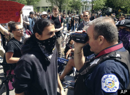 A Chicago police officer videotapes a verbal lashing from a protester outside the President Barack Obama's campaign headquarters in Chicago, Monday, May 21, 2012, on the final day of the NATO summit. (AP Photo/Robert Ray)