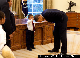President Barack Obama bends over so the son of a White House staff member can pat his head during a family visit to the Oval Office May 8, 2009. The youngster wanted to see if the President's haircut felt like his own. (Official White House Photo by Pete Souza)