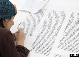 Julie Seltzer works on a Torah as part of the exhibit As It Is Written: Project 304,805 at the Contemporary Jewish Museum in San Francisco. (Bruce Damonte, courtesy of the Contemporary Jewish Museum)
