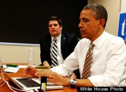 President Barack Obama answers questions on Twitter on Thursday in Newton, Iowa. Seated next to him is White House digital strategist Macon Phillips.