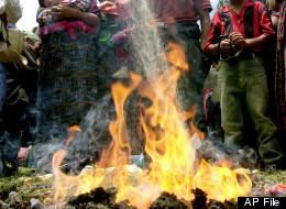 A Mayan priest thows sugar to the fire during a Mayan ceremony to commemorate the anniversary of a 1982 massacre of 184 people carried by the Guatemalan army during the regime of former dictator Efrain Rios Montt in Plan de Sanchez, a small village 200 km (125 miles) north of Guatemala City, Monday, July 19, 2004. (AP Photo/Rodrigo Abd)