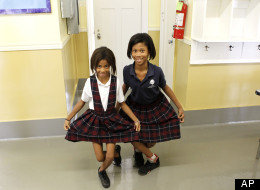 Alexandria Cole, 9. left, and Kaci Chairs, 9, right, curtsy in the hallway at the International School of Louisiana in New Orleans, Friday, Nov. 11, 2011.