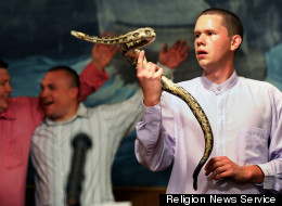 Andrew Hamblin, 21, pastor of Tabernacle Church of God in LaFollette, Tenn., looks into the eyes of a rattlesnake at the church alter while others sing songs during church service on April 13, 2012. RNS photo by Shelley Mays/courtesy USA Today