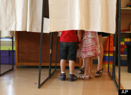 A French citizen with her children prepares her vote in a polling station in Nice, southern France, in the first round of the French parliamentary elections to elect the 14th National Assembly of the 5th Republic, Sunday, June 10, 2012.