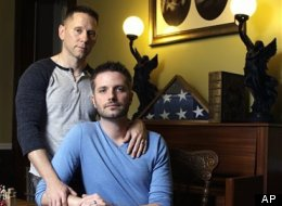 U.S. Army Reserve Capt. Stephen Hill (standing) and his husband, Joshua Snyder