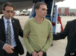 Luka Rocco Magnotta is taken by police from a Canadian military plane to a waiting van on Monday, June 18, 2012 in Mirabel, Quebec. Magnotta, the lone suspect in a brutal Montreal killing that made headlines around the world, is back home to face justice on Canadian soil. THE CANADIAN PRESS/HO