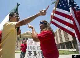 Andy Hernandez, carrying a Mexican flag, and Allison Culver, carrying an American flag, argue over SB 1070 outside the State Capitol Building in Phoenix, Ariz.