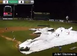 The grounds crew at Silver Cross Field in Joliet, Illinois struggle with a tarp and the wind during a rain delay.