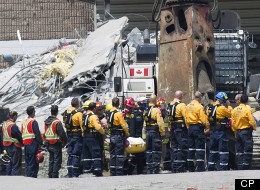 Rescue workers remove their hard hats as firefighters carry a second body out of the Algo Centre Mall in Elliot Lake, Ont., on Wednesday, June 27, 2012, after the mall's roof collapsed last Saturday. Provincial police in Ontario announce criminal investigation into the fatal mall roof collapse in Elliot Lake. THE CANADIAN PRESS/Nathan Denette